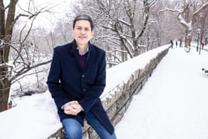 David Miliband sitting on low wall in snowy landscape