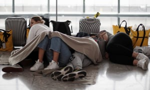 A group of young travellers on the floor of terminal five, neatly slotted together like spoons.