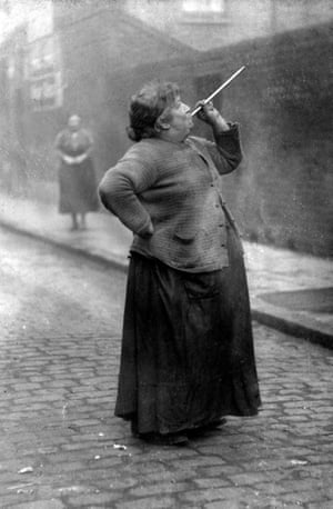 Mrs Mary Smith wakes the dockers of Limehouse, London, with her peashooter in 1927.