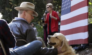 Bruce Mann pats a dog while his wife, Elizabeth Warren, speaks at a campaign event in Hanover, New Hampshire.