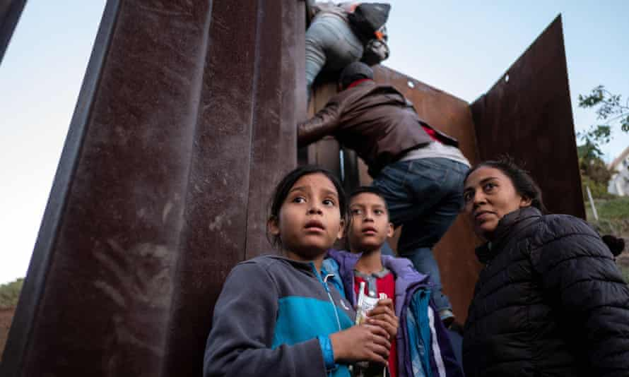 Central American migrants hesitate as others climb the Mexico-US border fence in an attempt to cross to San Diego county, in Playas de Tijuana, Baja California state, Mexico.