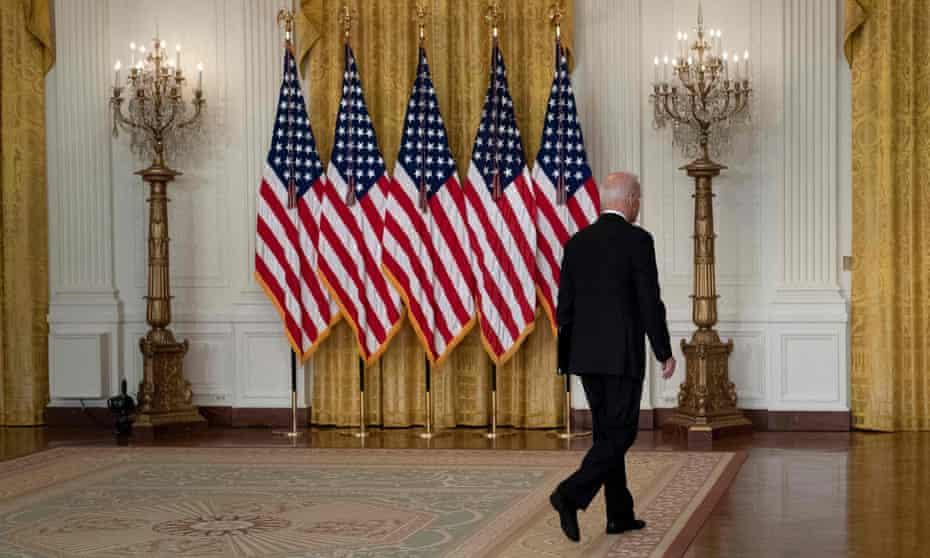 A view of President Joe Biden's back as he walks away. against a backdrop of US flags