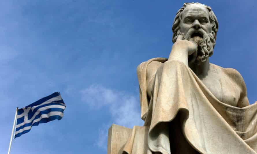 A Greek flag flutters by a statue of the philosopher Socrates in central Athens.