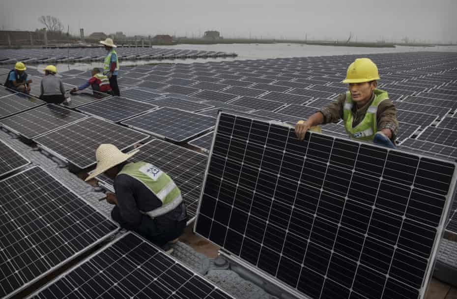 Chinese workers prepare panels that will be part of a large floating solar farm project under construction on a lake caused by a collapsed and flooded coal mine in Huainan, Anhui province, China.