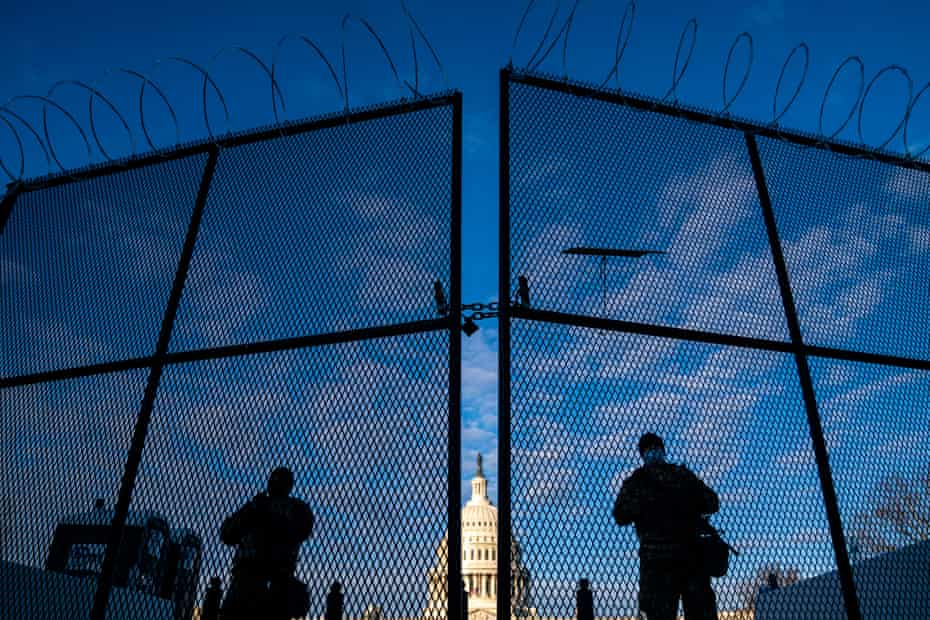 National Guard troops stand behind security fencing with the dome of the Capitol building behind them, on Saturday.