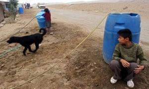 利马北部Pachacutec棚户区的居民从汽缸中取水到他们的房屋。