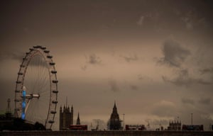 The sky darkens over the London Eye and the Houses of Parliament.