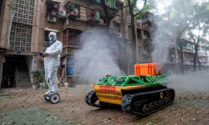 A volunteer operates a remote controlled disinfection robot to disinfect a residential area amid the Covid-19 coronavirus outbreak in Wuhan in China's central Hubei province on March 16, 2020.