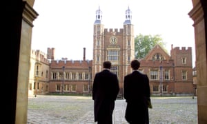 Two schoolboys walk into a courtyard at Eton.