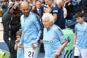 David Silva holds the hand of 102-year-old mascot Vera Cohen as they leave the tunnel ahead of Manchester City's match against Fulham at the Etihad Stadium.