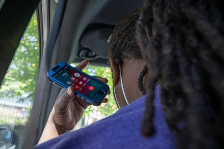 Anthony Scroggins holds his ear to his phone as he makes his way across Baltimore to meet with a Roca client suffering from a gunshot wound.