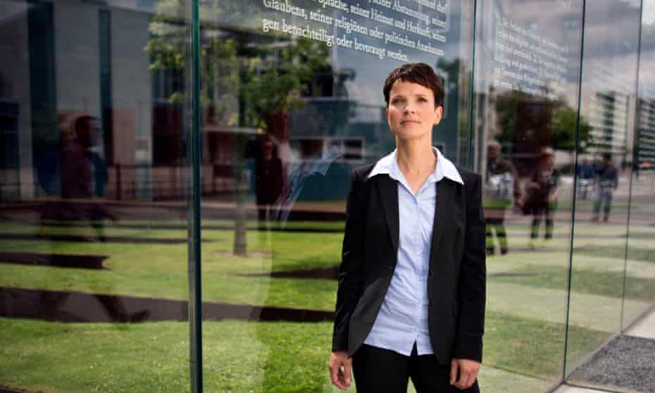 Frauke Petry of Alternative for Germany stands in front of glass panels engraved with text from the fundamental rights of Germany's Basic Law, the Bundestag, Berlin.