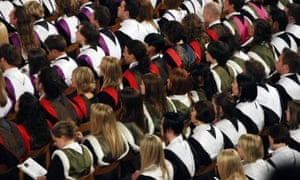 Students in gowns at a university graduation ceremony.