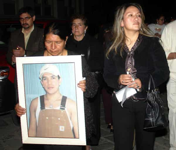 The mother and sister of Marcelo Lucero carry his portrait as they leave the church after his wake in Gualaceo, Ecuador.