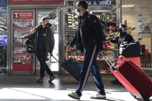 People carry skis as they arrive at Turin train station, Italy. Among other measures against Coronavirus spreading, the Italian government decided to close ski resorts all over the country