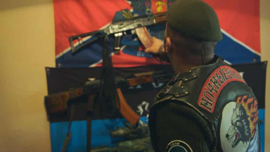 Russian Night Wolves biker Denis Kuznetsov with an AK-47 and the rebels' flag of Novorossiya