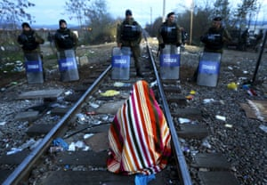 Hamid, 34, an electrical engineer from Sanandij, Iran, who is one of a dozen migrants on hunger strike, sits on rail tracks in front of Macedonian riot police guarding the border at Idomeni, Greece