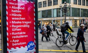 "Signs from Germany's health ministry remind people in Berlin of measures to reduce the risk of Covid-19. The sign says ""Social distancing, Hand washing, Wearing mask, Ventilate, Reduce social contacts, Use the Corona App""."