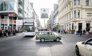 A sightseeing bus and a Trabant car, produced in the former East Germany, drive at an intersection on the site of Checkpoint Charlie, the Cold War's most famous border crossing between East and West Germany.