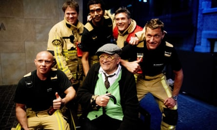 David Hockney poses with his rescuers after being stuck in the lift for 30 minutes.