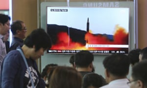 People watch a TV news program showing a file image of a missile launch by North Korea
