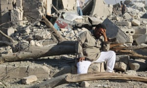 A Syrian man cries as he sits on the rubble of a building following a reported barrel-bomb attack by Syrian government forces