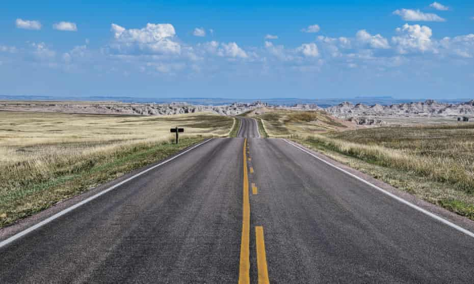 A road cuts through the Badlands National Park.