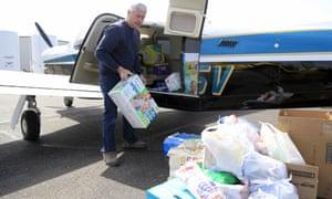 Pilot Herb Johansen of Bennington, Nebraska, unloads supplies he volunteered to fly into the Fremont airport, 18 March 2019.