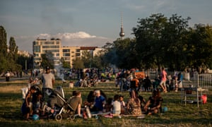 Visitors enjoy warm weather in Mauerpark in Berlin. Germany has seen a four-month high in new coronavirus cases.