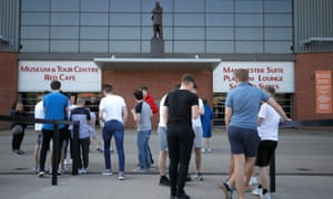 Fans gather at the Sir Alex Ferguson stand at United's Old Trafford football stadium.
