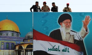 Iraqi security forces on top of a building covered with a poster of Iran's supreme leader Ayatollah Ali Khamenei, who last week 'decided to set the record straight. This was in sum the pursuit of an arms control agreement, he said.'