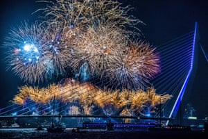 People celebrate the New Year with a firework show at the Erasmusbrug in Rotterdam, the Netherlands