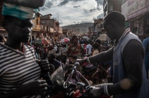 A taxi driver pushes his motorbike through a crowded market in the city of Butembo