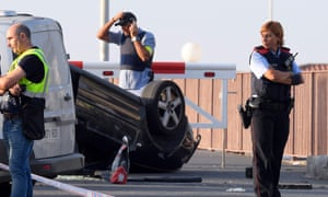 The presumed terrorists' car, lying overturned on the seafront road in Cambrils.