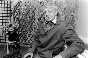 anthony burgess seated and smoking in a courtyard in 1987