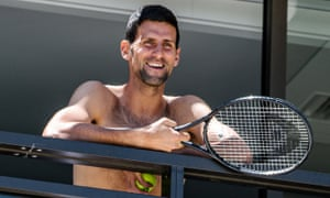 Novak Djokovic smiles at fans from his hotel balcony in Adelaide
