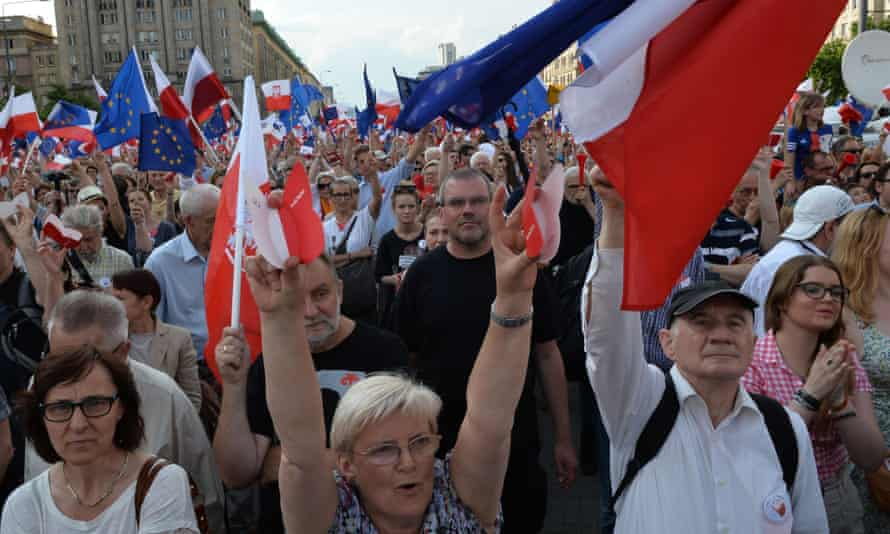 People carry Polish flags as they protest the policies of right-wing Law and Justice government, on the 27th anniversary of partly free elections that led to overthrowing communism.