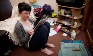 A young woman UK university student reading a book in the living room of her house flat bedsitC2M2G1 A young woman UK university student reading a book in the living room of her house flat bedsit