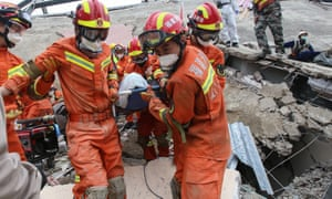 A man is rescued from the rubble of a collapsed hotel used as a coronavirus quarantine centre in Quanzhou, in China's eastern Fujian province.