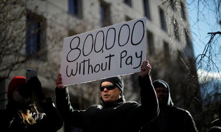 """A demonstrator holds a sign at the """"Rally to End the Shutdown"""" in Washington, DC."""