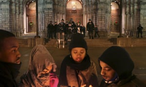 St Louis Police officers guard the entrance to the Cathedral Basilica as protesters hold candlelight vigil on Christmas Eve.