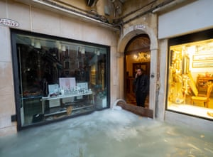 A shop worker watches the water outside her door