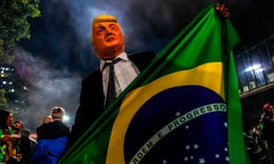 A supporter  presidential election winner Jair Bolsonaro wears a mask of Donald Trump