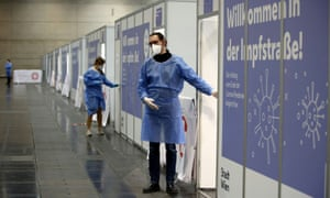 People wait for vaccinations in Vienna, Austria, in front of signs reading 'Welcome to vaccination street'.
