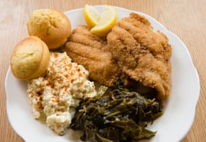 A plate of cajun-fried catfish is served with Miss Betty's potato salad and fresh collard greens at Florida Avenue Grill in Washington DC.