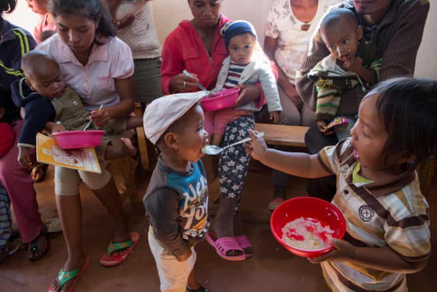 Mothers (and a father) and their malnourished children eat a meal of rice, marrow, dried shrimp, carrots, oil and iodised salt during a nutrition class in Antsirabe