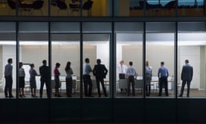 View of business people standing in conference room from outdoors.