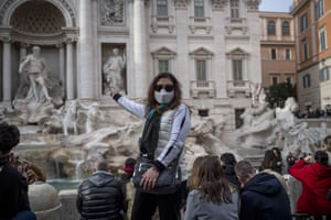 Tourists wearing face masks visit the Fontana di Trevi in Rome, Italy.