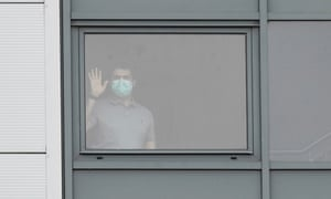 A person wearing a mask stands at a window of a staff accommodation block at Arrowe Park hospital.