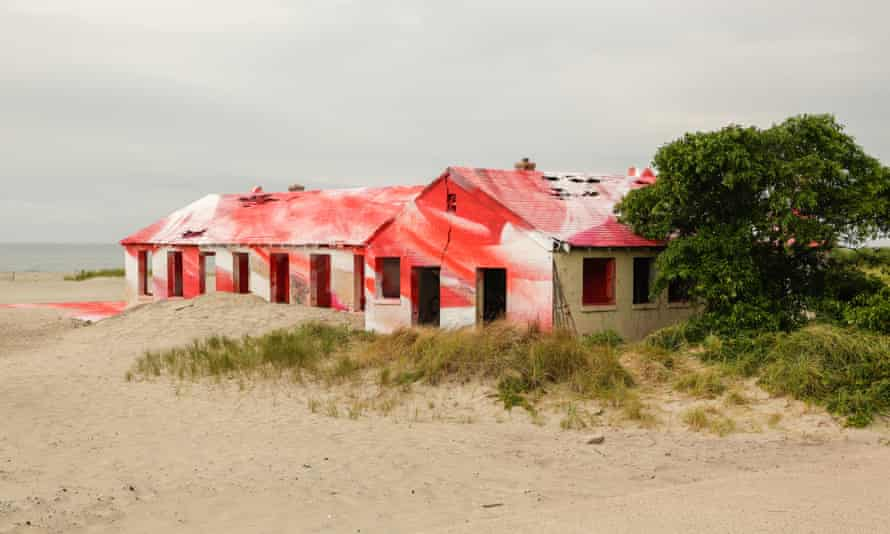 The building, which was painted over a week, peeps out of the sand.